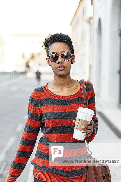 Portrait of young woman with coffee to go wearing sunglasses and striped pullover