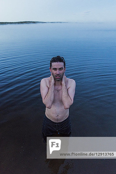 Man with bare chest standing in lake,  washing his neck