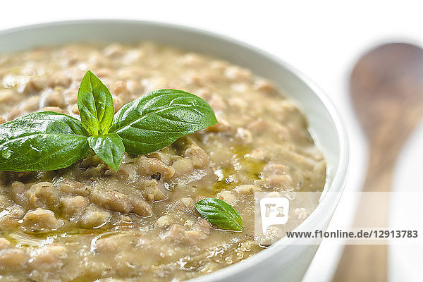 Barley soup with olive oil and basil  close-up