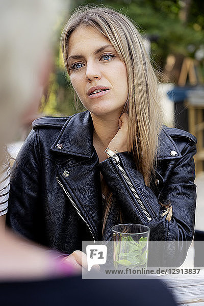 Portrait of a young woman sitting in beer garden  looking at a friend