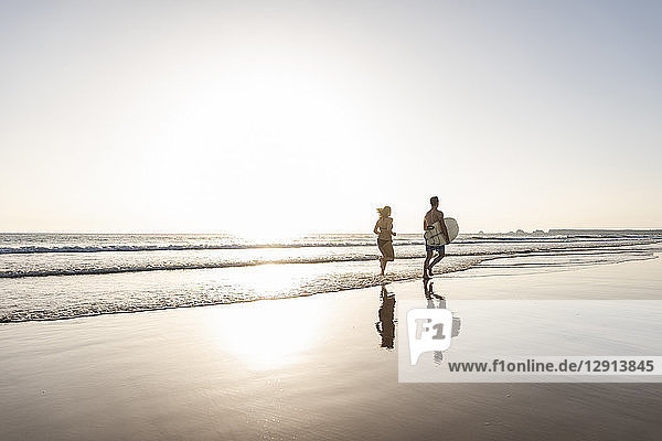 Young couple running on beach  carrying surfboard