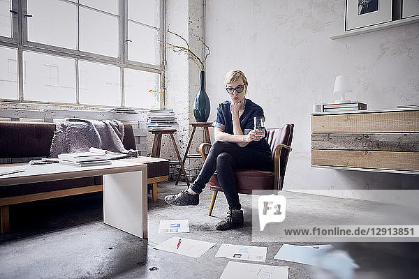 Woman sitting on arm chair in loft looking at papers on the floor