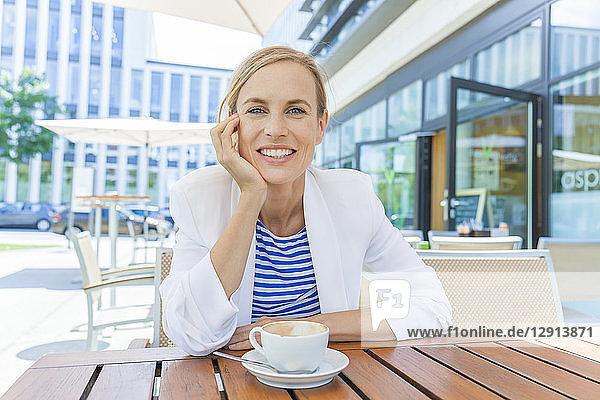 Smiling blond businesswoman at sidewalk cafe