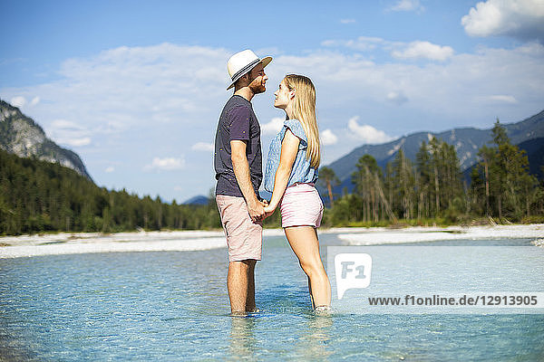 Young couple standing in water  holding hands