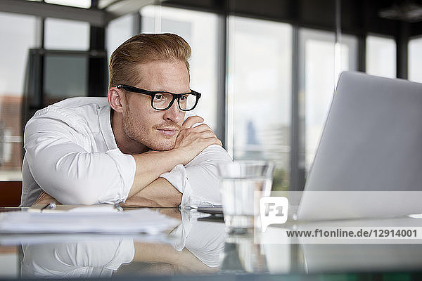 Businessman leaning on desk in office with laptop