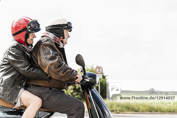Happy senior couple riding motor scooter
