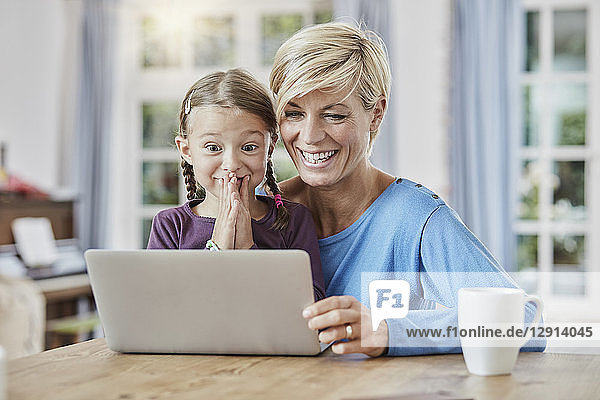 Mother and surprised daughter using laptop at home
