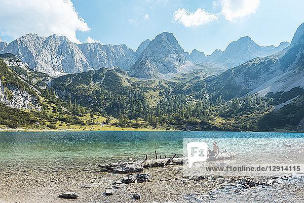 Austria  Tyrol  Young man at Lake Seebensee sitting on tree trunk