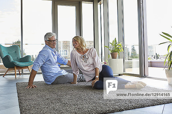 Smiling mature couple relaxing at home sitting on carpet