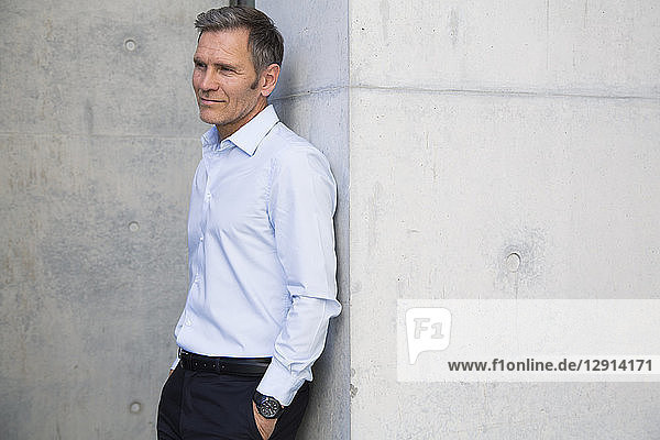 Mature businessman leaning against a wall