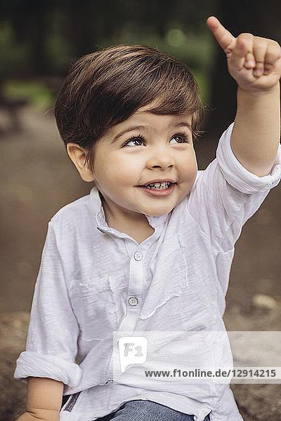 Portrait of smiling toddler raising his finger