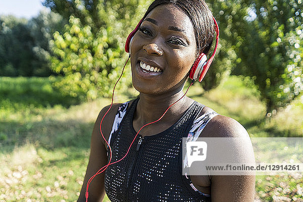 Young athlete in nature  listening music with headphones