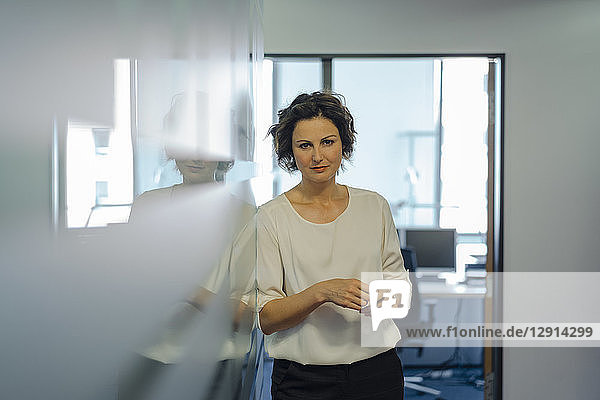 Shy businesswoman standing in office