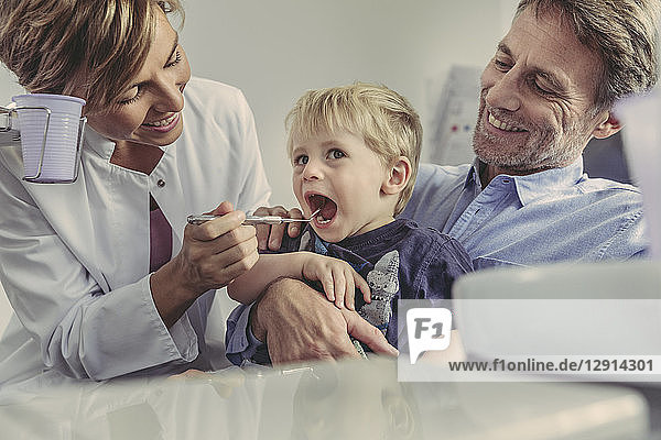 Female dentist examining little boy  sitting on his father's lap