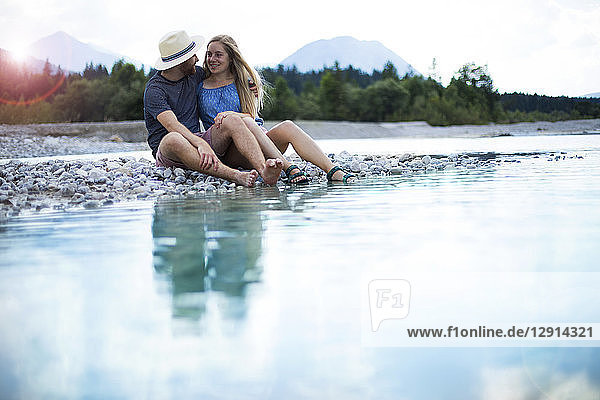 Young couple sitting at riverside