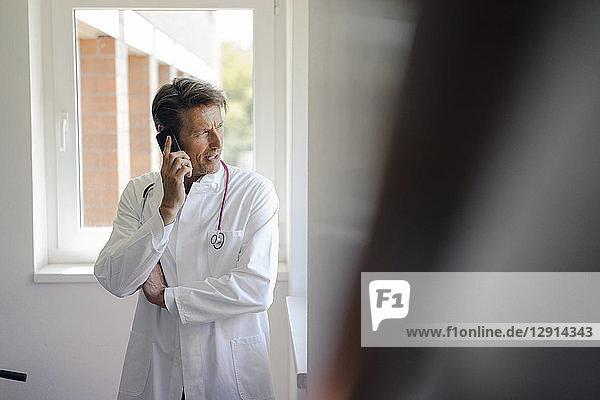 Doctor standing in hospital  using smartphone