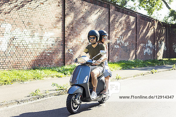 Couple riding motor scooter in summer