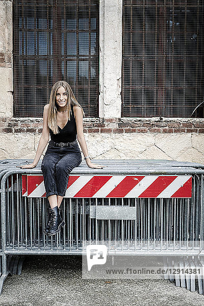 Portrait of smiling teenage girl sitting on barriers in the city