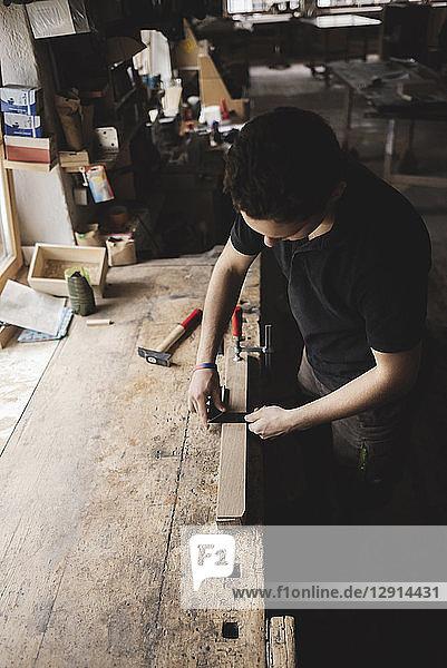 Carpenter measuring piece of wood in workshop