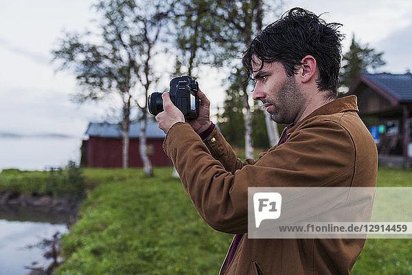 Sweden  Kiruna  Young man taking pictures of lake