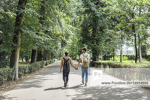 Back view of young gay couple with backpacks walking hand in hand on a road