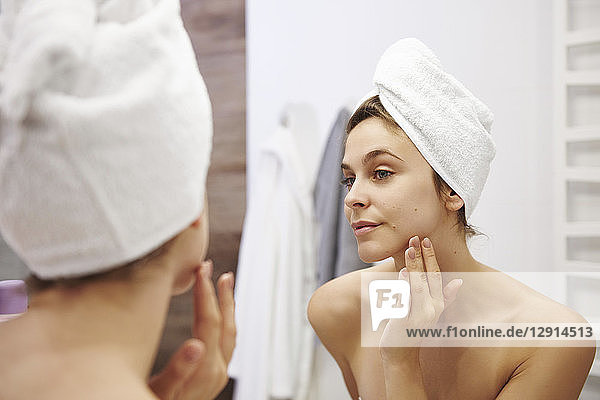 Mirror image of young woman examining her face in the bathroom