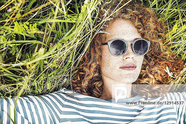 Portrait of young woman relaxing on a meadow wearing sunglasses