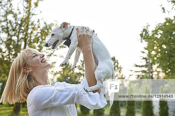 Happy woman holding dog wearing a bowtie outdoors