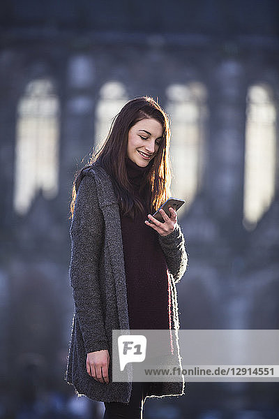Portrait of smiling young woman looking at cell phone in autumn