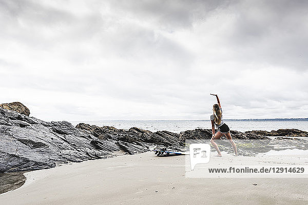 Young woman with surfboard stretching on the beach