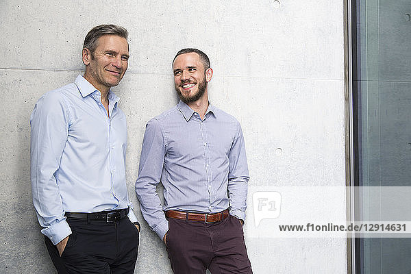 Portrait of two smiling businessmen at a wall