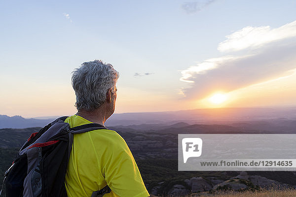 Spain  Catalonia  Montcau  senior man looking at view from top of hill during sunset