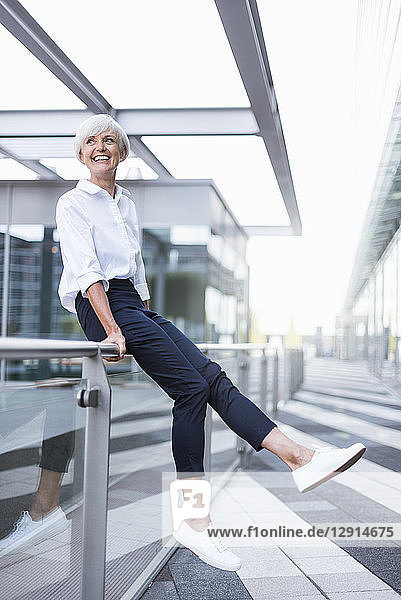 Happy senior woman sitting on railing in the city looking around
