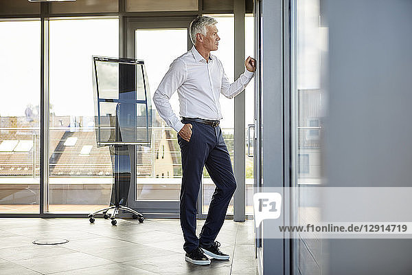 Worried businessman standing in office  looking out of window