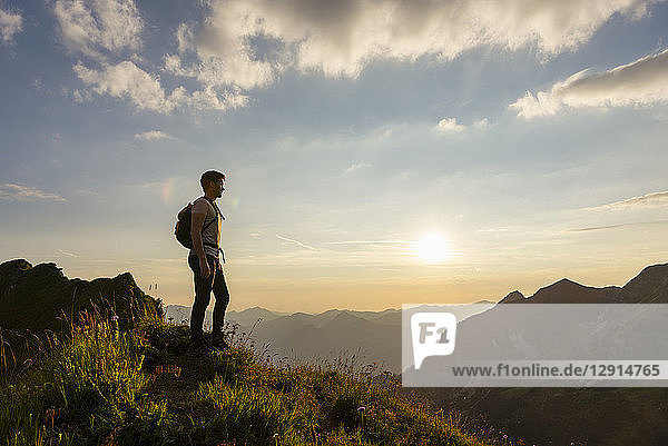 Germany  Bavaria  Oberstdorf  man on a hike in the mountains looking at view at sunset