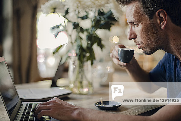 Mid adult man sitting in coffee shop  drinking coffee  using laptop