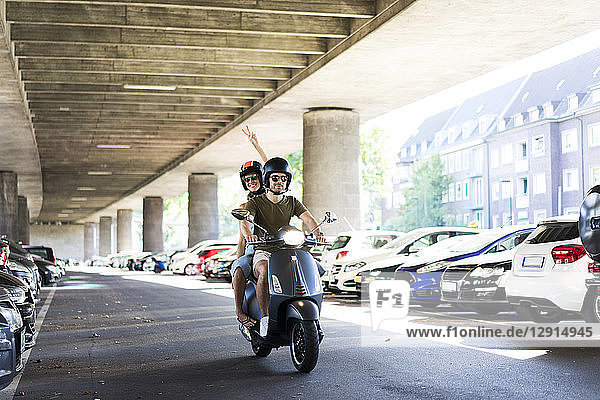 Happy couple riding motor scooter at underpass