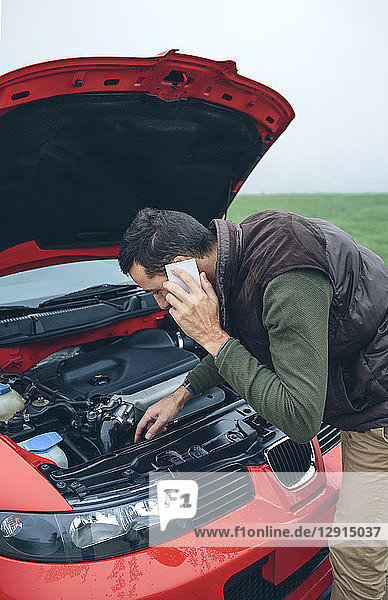Man on cell phone looking at broken engine car