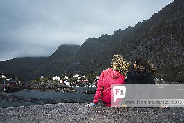 Norway  Lofoten  rear view of two young women sitting on a pier at the coast