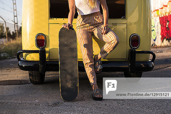 Young woman with skateboard standing outside at a vintage van