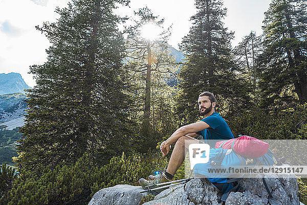 Austria  Tyrol  Hiker taking a break  sitting on a rock
