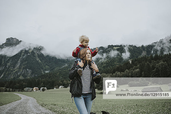 Austria  Vorarlberg  Mellau  mother carrying toddler on shoulders on a trip in the mountains