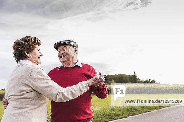 Happy senior couple dancing on country road