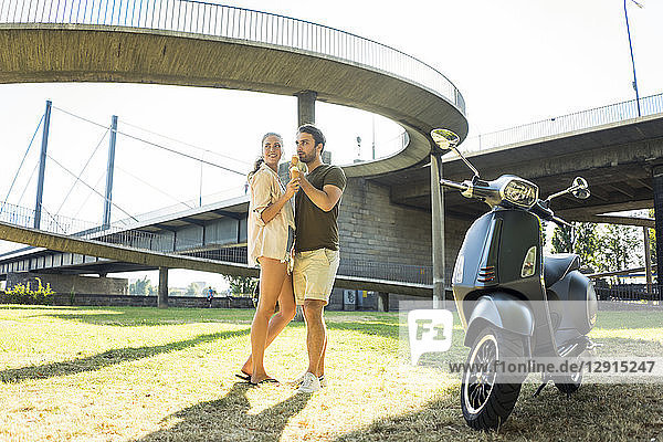 Happy couple with motor scooter in summer eating ice cream