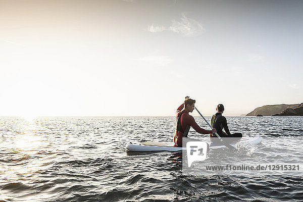 Couple on paddling on paddleboard at sunset on the sea