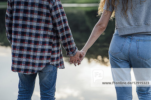 Romantic couple standing at the riverside  holding hands