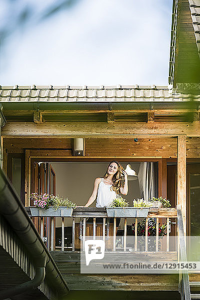 Portrait of smiling woman standing on balcony