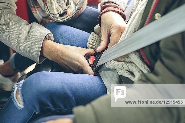 Close-up of woman fastening safety seat belt of girl sitting in a car