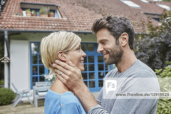 Happy affectionate couple in front of their home