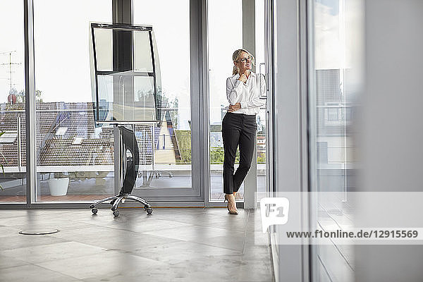 Successful businessman standing in office  looking out of window